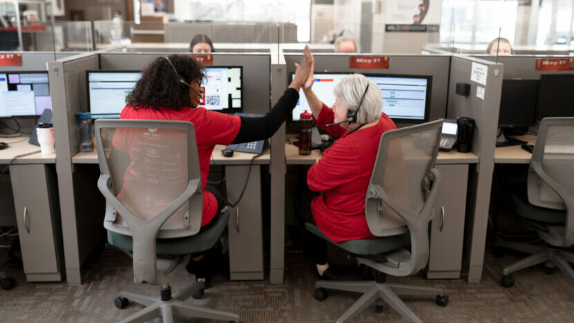 Two call centre colleagues high-fiving
