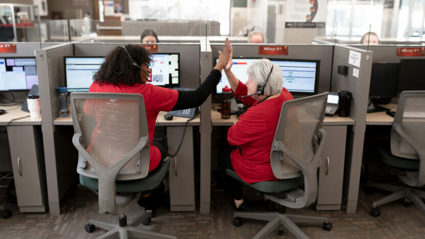 Two call-centre colleagues high-fiving