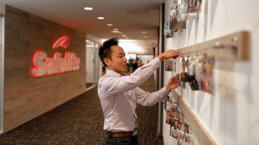 Safelite employee pinning team photographs to wall