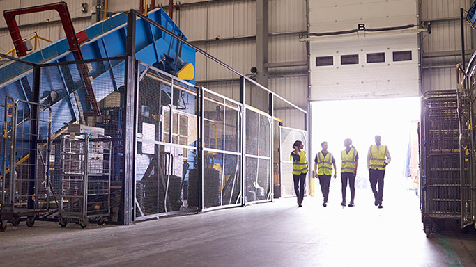 Four employees in high vis jackets walking into warehouse