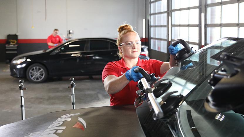 Technician fitting windscreen