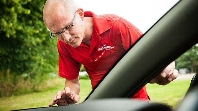 Belron employee inspecting windscreen