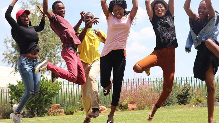 Afrika Tikkun beneficiaries jumping in the air